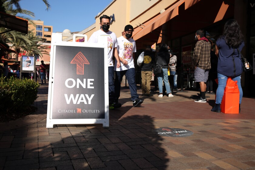 People walk against the suggested flow of foot traffic at an outdoor mall