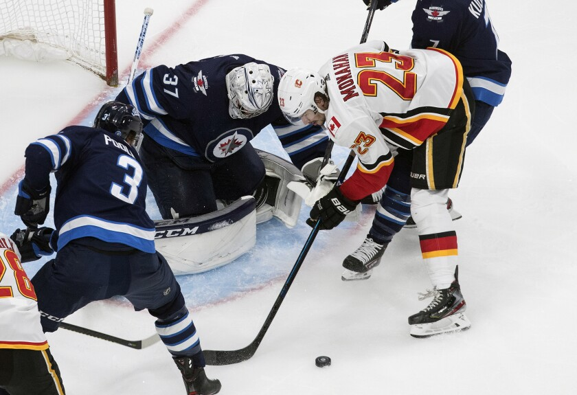 Calgary Flames' Sean Monahan (23) is stopped by Winnipeg Jets goalie Connor Hellebuyck (37) during the second period of an NHL qualifying round game, in Edmonton, Alberta, Thursday, Aug. 6, 2020. (Jason Franson=/The Canadian Press via AP)