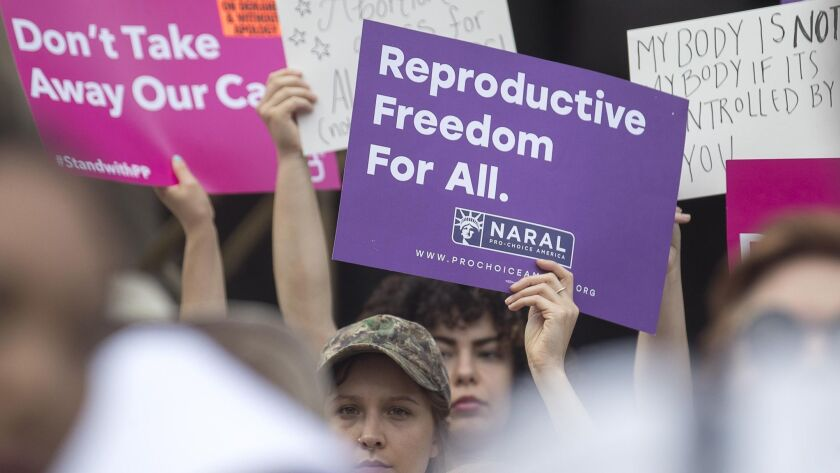 Anti-abortion protestors rally outside of the Georgia State Capitol following the signing of HB 481,