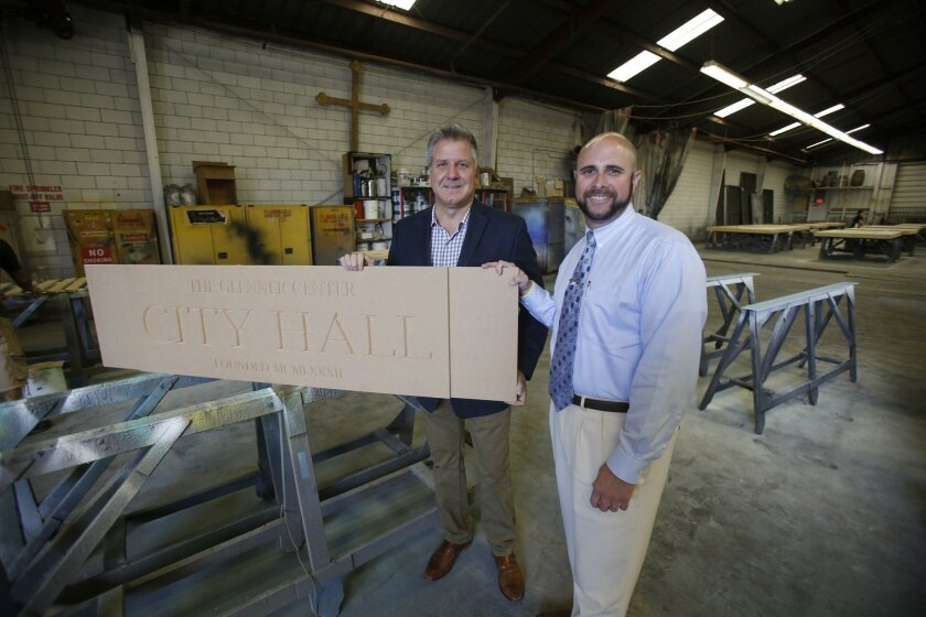 San Diego Opera General Director David Bennett, left, and Scott Tarde, CEO of George G. Glenner Alzheimer's Family Centers, hold the nameplate for the first building in Town Square, an indoor miniature memory city being built for Alzheimer's and dementia patients inside a Chula Vista industrial bui