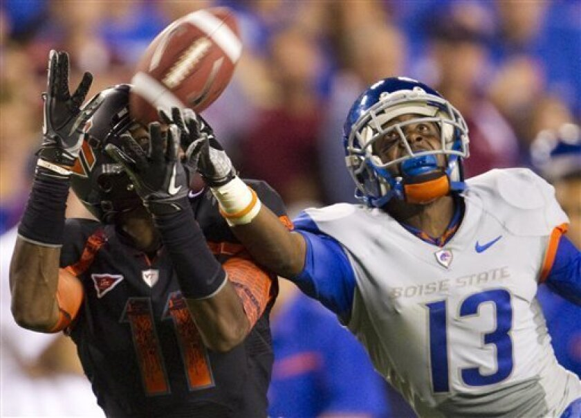 Boise State cornerback Brandyn Thompson (13), right, defends a deep pass against Virginia Tech wide receiver Dyrell Roberts (11) in the final minute of the fourth quarter of an NCAA college football game on Monday, Sept. 6, 2010 in Landover, Md. Boise State won the game 33-30. (AP Photo/Evan Vucci)