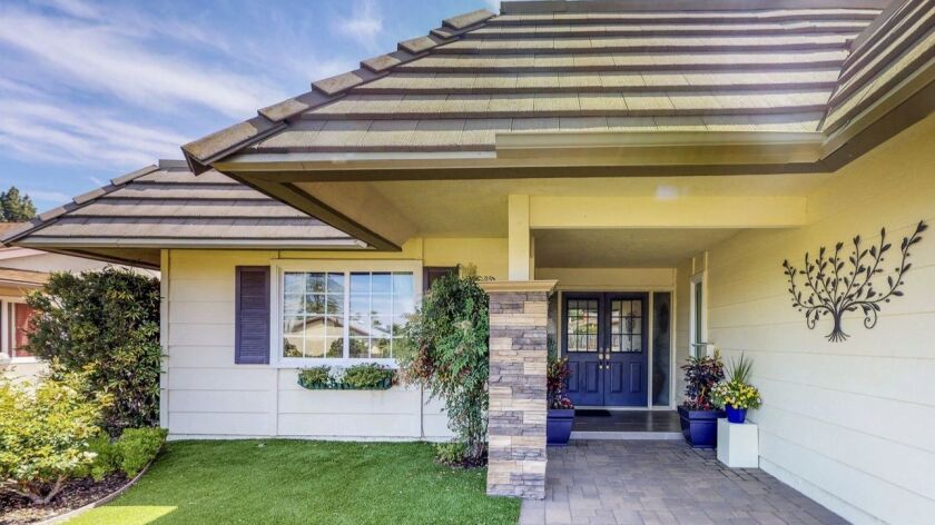 A rich blue front door and planters create curb appeal for this listing.