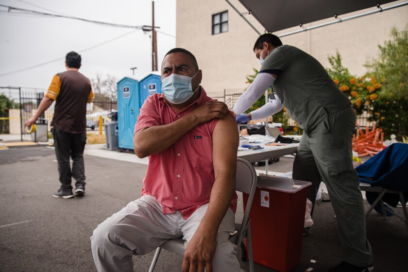 Fred Valencia rolls up a sleeve for a vaccine outside the Logan Heights Family Health Center in Barrio Logan on April 3.