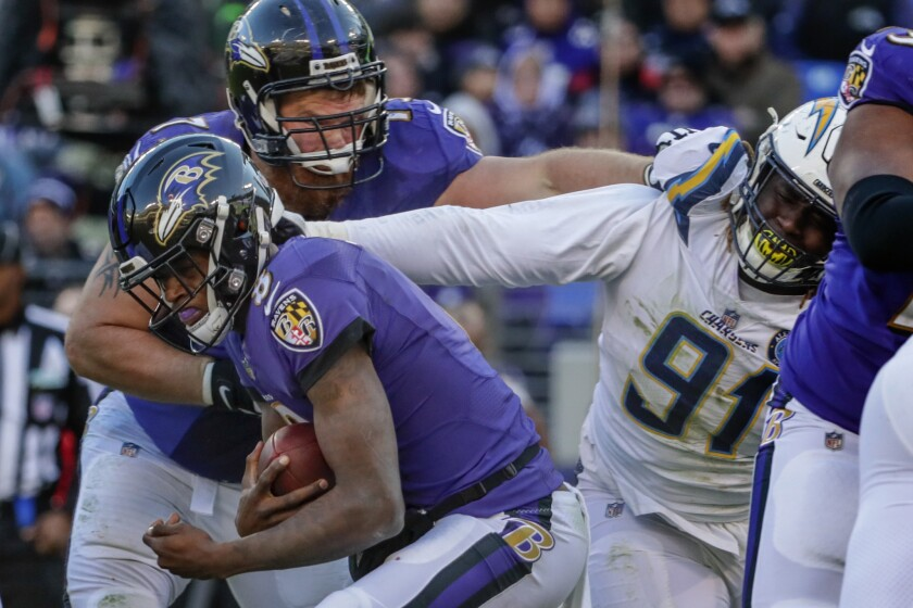The Chargers' Justin Jones grabs Ravens quarterback Lamar Jackson during their AFC playoff game in January.
