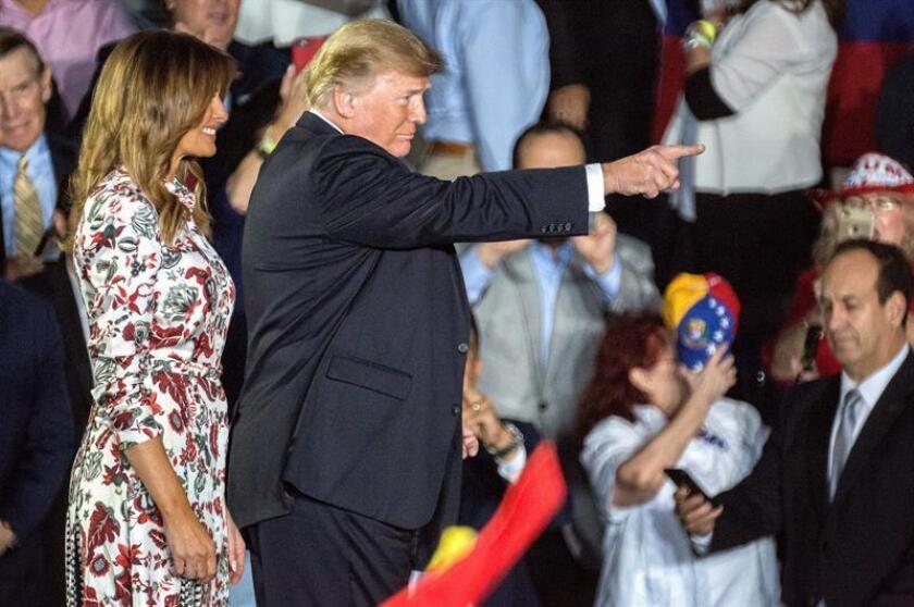 El presidente de los Estados Unidos, Donald J. Trump (c), y su esposa, la primera dama Melania Trump (i), saludan a la comunidad venezolano-estadounidense, este lunes en la Universidad Internacional de Florida, en Miami, Florida (EE. UU.). EFE