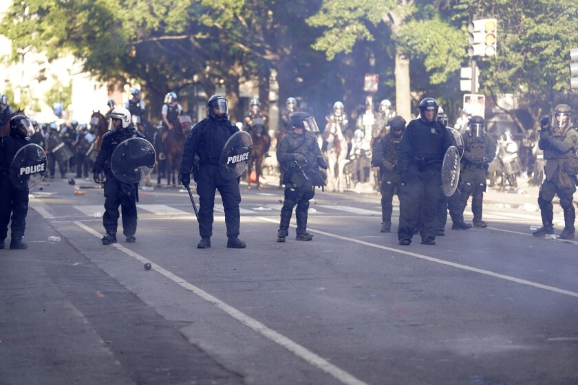 In this June 1, 2020, photo, police stand in smoke as they clear the area Lafayette Park as demonstrators gather to protest the death of George Floyd, near the White House in Washington. The Trump administration's use of smoke bombs and pepper balls to rout civil rights demonstrators from Lafayette Park near the White House has added a new chapter to the site's storied history as a soapbox for social and political unrest. (AP Photo/Evan Vucci)