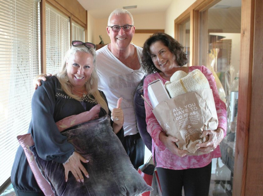 Kirsten Harrison-Jack (left) collects household items for Shauna donated by Bird Rock residents Brian Hilliard and Arielle Ford.