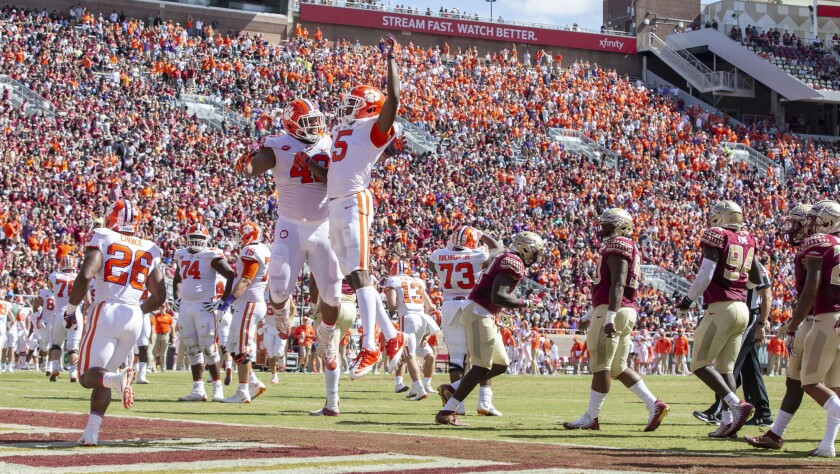 Clemson wide receiver Tee Higgins (5) and lineman Christin Wilkins celebrate Higgins' touchdown against Florida State in the first half on Saturday.