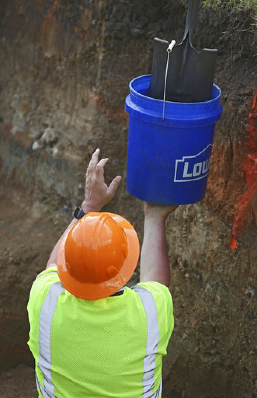 Historian Scott Ellsworth hands up a bucket with items in it from a dig site at Oaklawn Cemetery, Wednesday, July 15, 2020, in Tulsa, Okla., during a test excavation in the search for possible mass graves from the 1921 Tulsa Race Massacre. (Mike Simons/Tulsa World via AP)