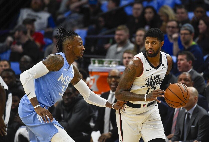 Clippers forward Paul George, right, tries to drive past Minnesota Timberwolves forward Robert Covington during the first half on Friday in Minneapolis.