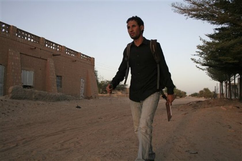 In this image taken on Saturday Feb. 2, 2013, Baba Ahmed, 26, AP's correspondent in Bamako, walks in his neighborhood in Timbuktu, Mali, days after it was liberated by French forces. In Baba Ahmed's own words, not a single light could be seen in my hometown of Timbuktu as we approached it at night just days after it was liberated from the al-Qaida-linked militants who ruled for nearly 10 months. The last time Baba had visited was in May, a month after the Islamic rebels seized Timbuktu. After my visit I covered my hometown's plight for The Associated Press from the distant capital of Bamako, straining for information over the telephone each week about what had become of this city I love. (AP Photo/Harouna Traore)