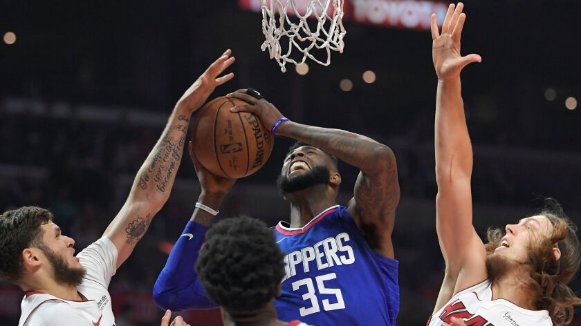 Clippers center Willie Reed shoots while defended by Miami's Tyler Johnson, left, Josh Richardson and Kelly Olynyk on Sunday.