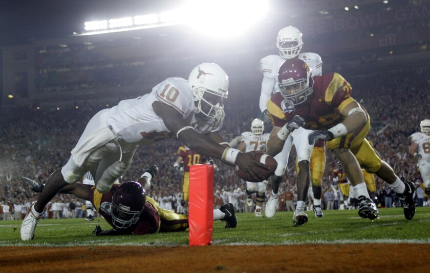 Texas quarterback Vince Young reaches the ball across the end zone for one of his three rushing touchdowns against USC in the BCS championship game at the Rose Bowl on Jan 4, 2006.