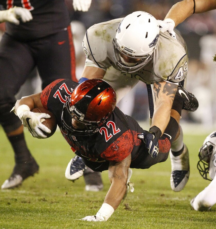 The Aztecs' Chase Price dives for more yardage as Nevada's Jordan Dobrich falls on top of him during the third quarter.