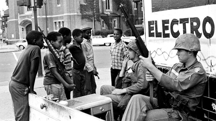 Soldiers from the U.S. Army's 82nd Airborne chat with kids on West Grand Boulevard as the violence subsided after five days of rioting.