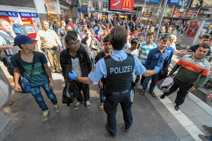 An officer shows a refugee group the way to the registration office at the central train station in Munich, Germany.