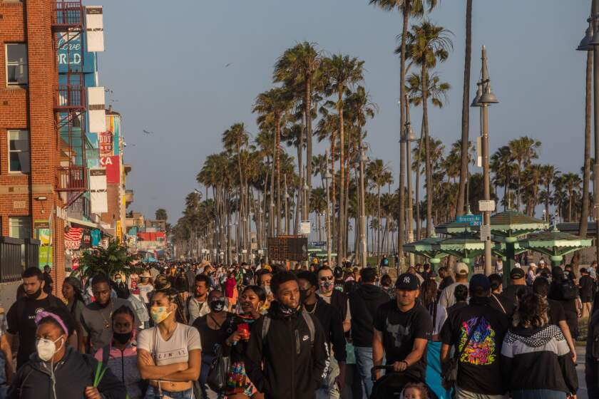People fill the boardwalk in Venice Beach during the first day of the Memorial Day holiday weekend.