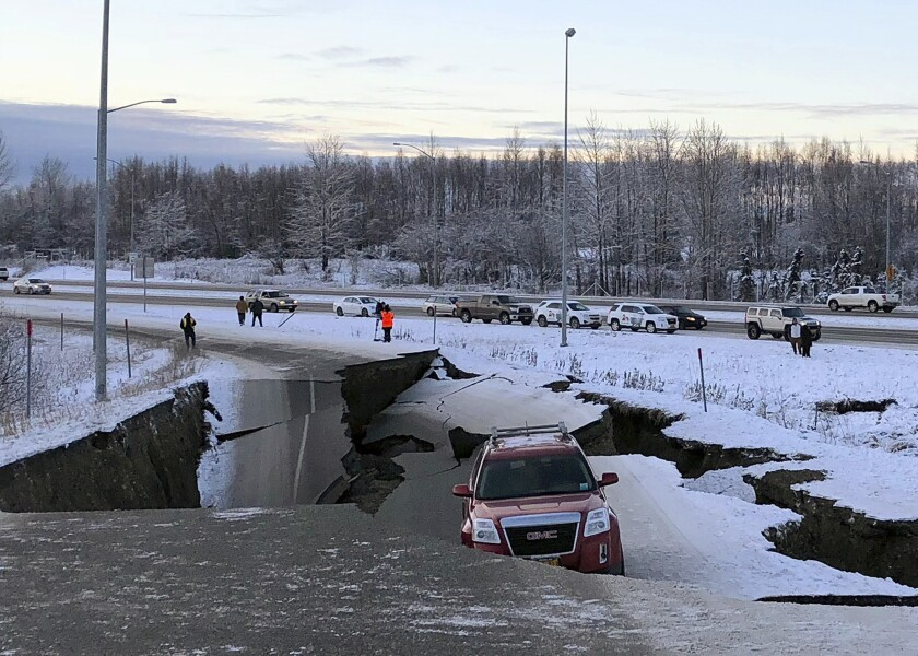 A car is trapped on a collapsed section of the off-ramp of Minnesota Drive in Anchorage, Friday. An earthquake measuring 7.0 and aftershocks rocked buildings and buckled roads.