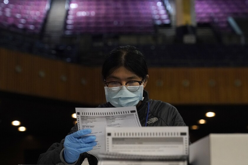 San Francisco Department of Elections worker Rosy Chan checks for damaged ballots at a voting center in San Francisco, Sunday, Nov. 1, 2020. (AP Photo/Jeff Chiu)