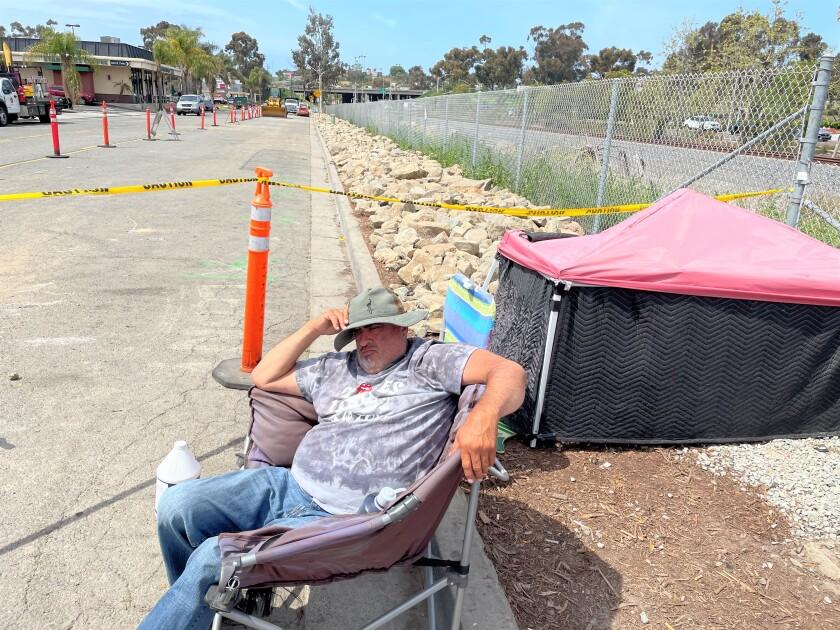 Tony Ramirez, homeless, sits near his tent alongside South Oceanside Boulevard.