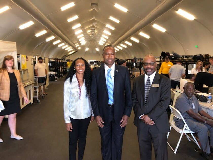 In this file photo from last year, Veterans Village of San Diego Homeless Shelter Director Lakesha Jones, U.S. Department of Housing and Urban Development Ben Carson and VVSD Executive Vice President Andre Simpson (left to right) are shown inside a bridge shelter tent that Veterans Village since has closed. The tent has been donated to the city of Chula Vista.