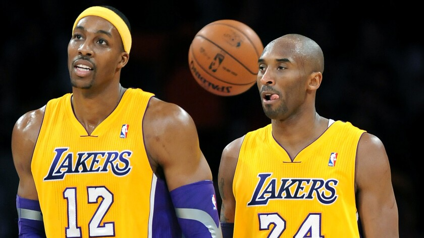 Lakers teammates Dwight Howard, left, and Kobe Bryant walk off the court during a game against the Milwaukee Bucks in January 2013.
