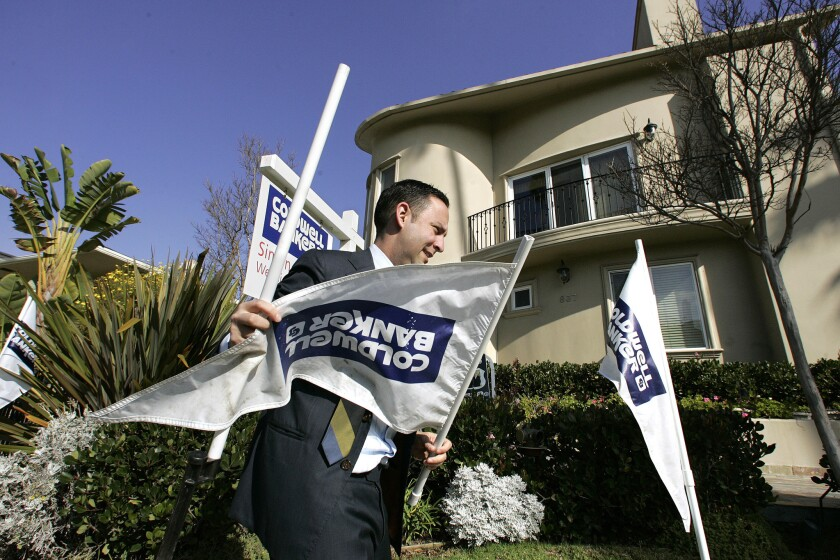 The firm that owns Coldwell Banker and other large real estate brokerages gave a dim prognosis for 2014 home sales May 5. Above, an agent puts signs outside a Santa Monica condo for sale in 2009.