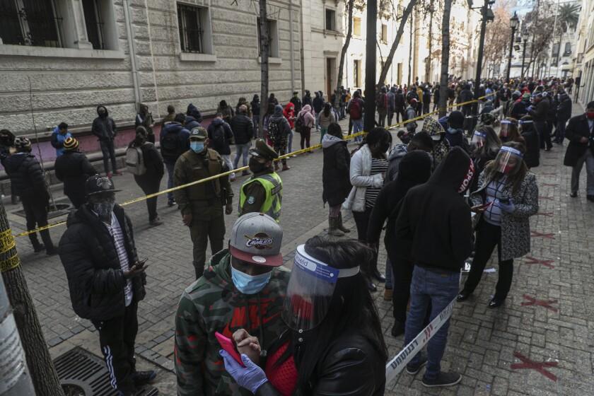 Cientos de personas forma una fila para obtener un porcentaje de sus fondos de ahorro para el retiro, en esta fotografía de archivo del jueves 30 de julio de 2020, en Santiago de Chile. (AP Foto/Esteban Felix)