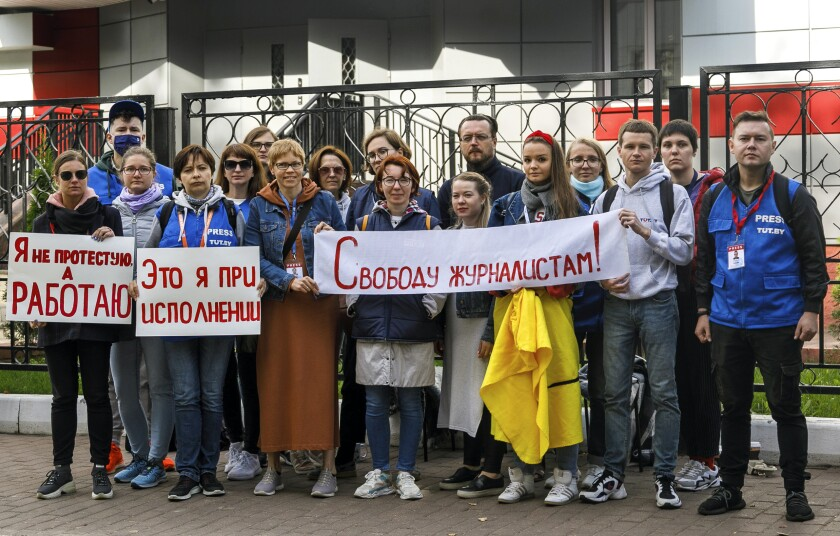 """Journalists of Belarusian TUT.BY media outlet hold banners reading """"I don't protest but work"""", """"This is me at work"""", """"Freedom for journalists!"""", from left to right, as they stand in front of police station in Minsk, Belarus, Wednesday, Sept. 2, 2020. Some dozen Belarusian journalists went out on Wednesday night to the building of the district police department to protest against the detention of their colleagues covering the dispersal of a student rally in the Belarusian capital. (Tut.By via AP)"""