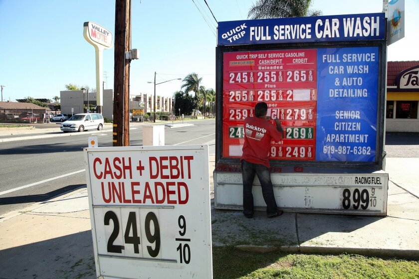 El Cajon, CA_2/9/2015_A gas station attendant changes the price on a grid of prices at a Quik Trip in El Cajon, CA during the recent rundown and accompanying runup of prices in 2015.  John Gastaldo/U-T San Diego/Zuma Press