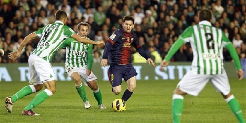 Barcelona's Leo Messi of Argentina, second right, and Betis's Nacho Perez, second left, vie for the ball during their La Liga soccer match at the Benito Villamarin stadium, in Seville, Spain, Sunday, Dec. 9, 2012. (AP Photo/Angel Fernandez)