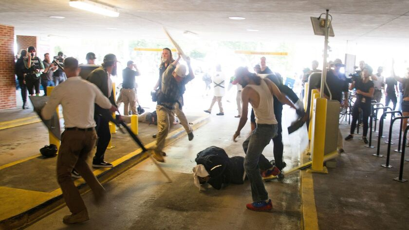 In this Saturday, Aug. 12, 2017 photo, DeAndre Harris, bottom is assaulted in a parking garage besid