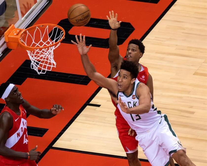 El guardia de los Milwaukee Bucks, Malcolm Brogdon (frente), tira a la canasta frente al guardia de los Toronto Raptors Kyle Lowry durante un partido de baloncesto de la NBA entre Toronto Raptors y Milwaukee Bucks, este jueves, en Toronto (Canadá). EFE