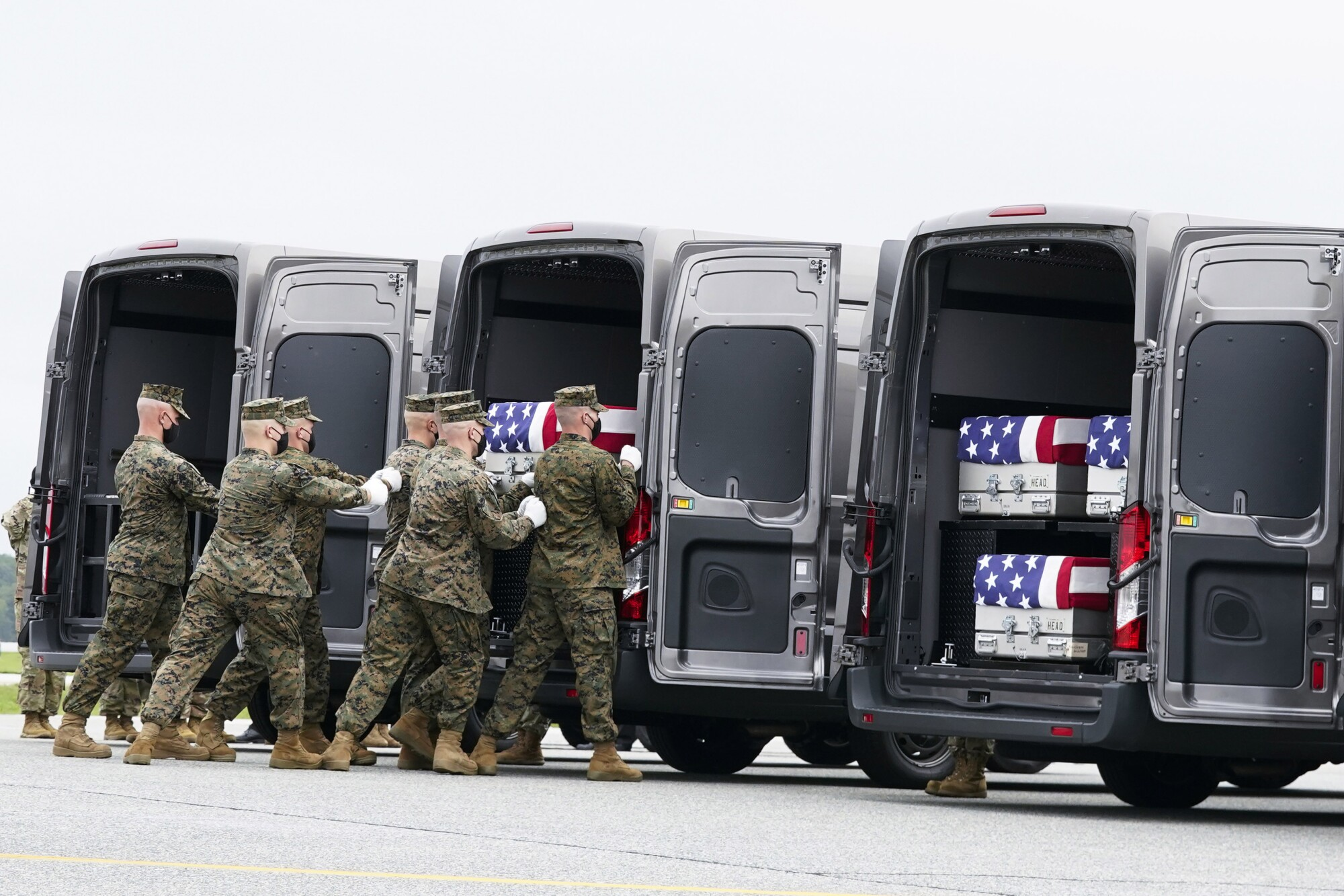 A team transfers the remains of a fallen Marine to a transport vehicle.