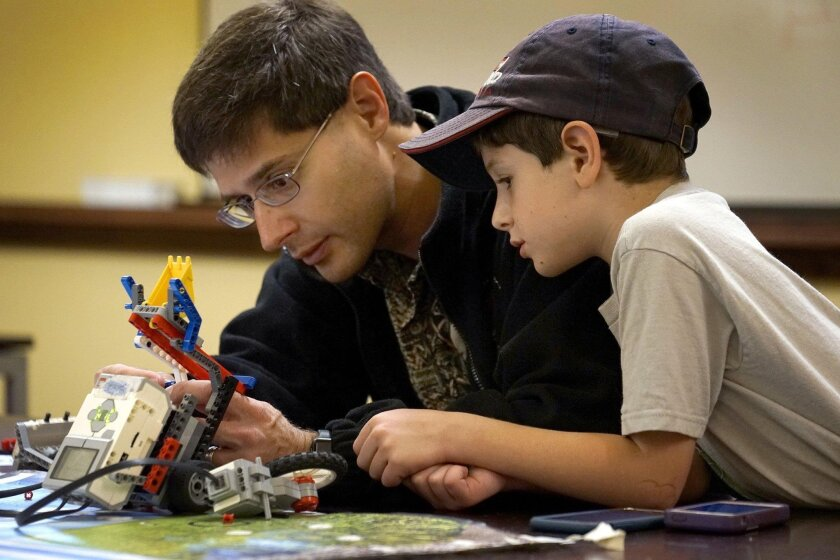 2466854_sd_me_kid_code_NL    June 05,  2016  San Diego, CA   Photo by Nancee E. Lewis / Nancee Lewis Photography  Aiden Gruby, 9, and his dad, Scott Gruby, from the Clairemont neighborhood, work on creating a Lego  motorize robotic construction during the Kids That Code: STEM Classes for Kids At th