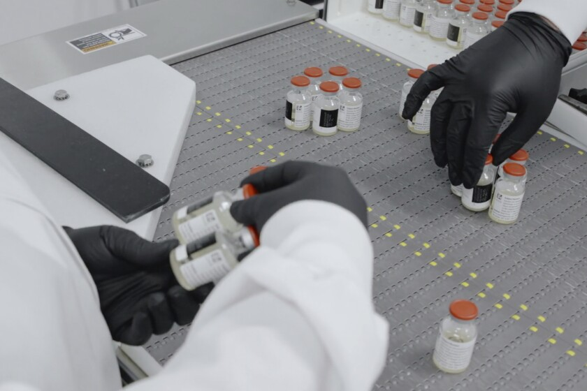 Workers at Regeneron Pharmaceuticals inspect vials of the company's experimental antibody treatment for COVID-19.