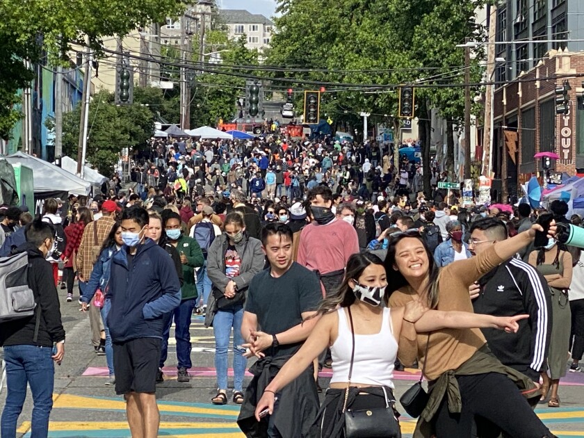 Two women celebrate in Seattle's protest zone June 13, as the area took on trappings of a street festival.