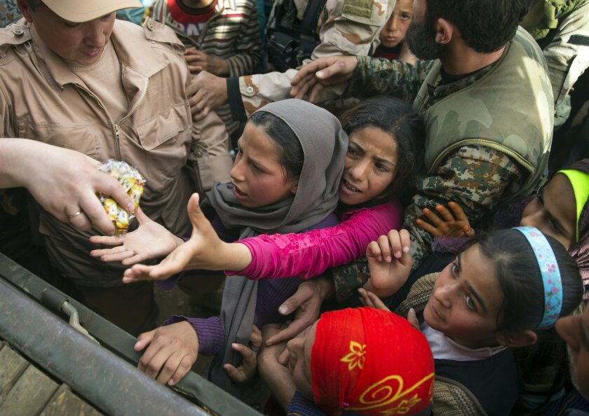 Children reach out for sweets distributed by Russian military in Maarzaf, about 15 kilometers west of Hama, Syria, Wednesday, March 2, 2016. The Russian- and U.S.-brokered cease-fire that began Saturday is intended to help pave the way for Syria peace talks planned for next week in Geneva. (AP Phot