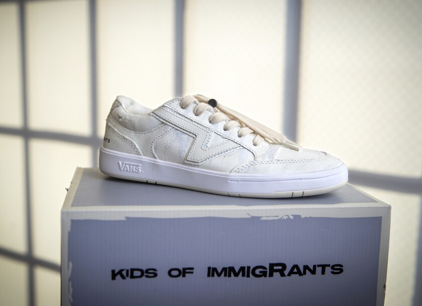 A white sneaker sitting on a shoe box.