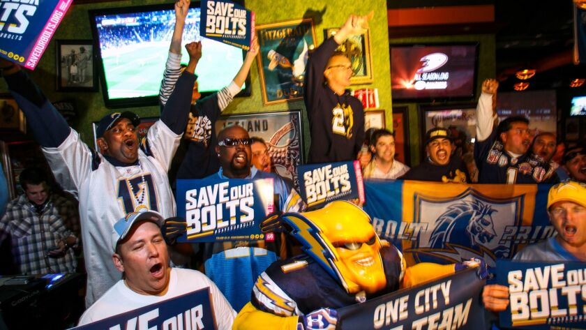 """Chargers fans, including Boltman, center, chant """"Save our Bolts"""" during a press conference put on by fans at the Tilted Kilt Mission Valley."""