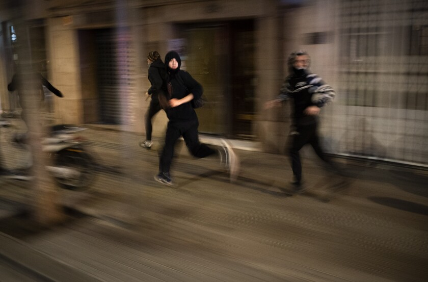 Protesters run away from police during clashes following a protest condemning the arrest of rap singer Pablo Hasél in Barcelona, Spain, Saturday, Feb. 27, 2021. Protests in support of the jailed rapper turned violent in Barcelona on Saturday with clashes between police and groups of mostly angry youths in the center of the Spanish city. (AP Photo/Emilio Morenatti)