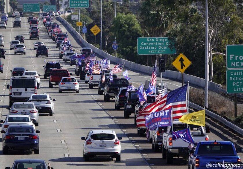 A long line of cars decorated in Trump flags and U.S. flags moves slowly on the freeway.