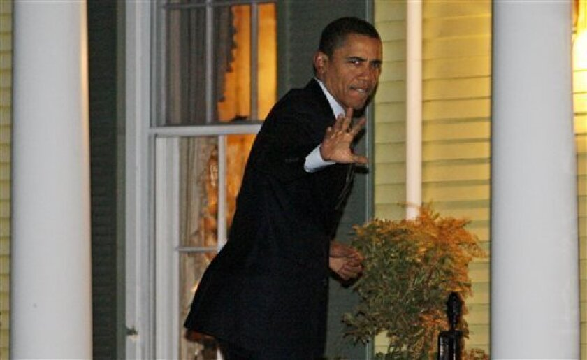 President-elect Barack Obama waves to reporters as he arrives at a private residence for a dinner in Chevy Chase, Md.,  Tuesday, Jan. 13, 2009. (AP Photo/Charles Dharapak)