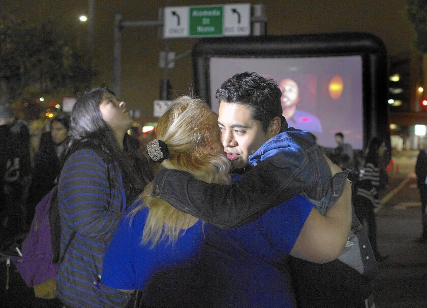 Armando Ibañez, 32, hugs a friend after President Obama's immigration address. The new policy won't help him and his mother.