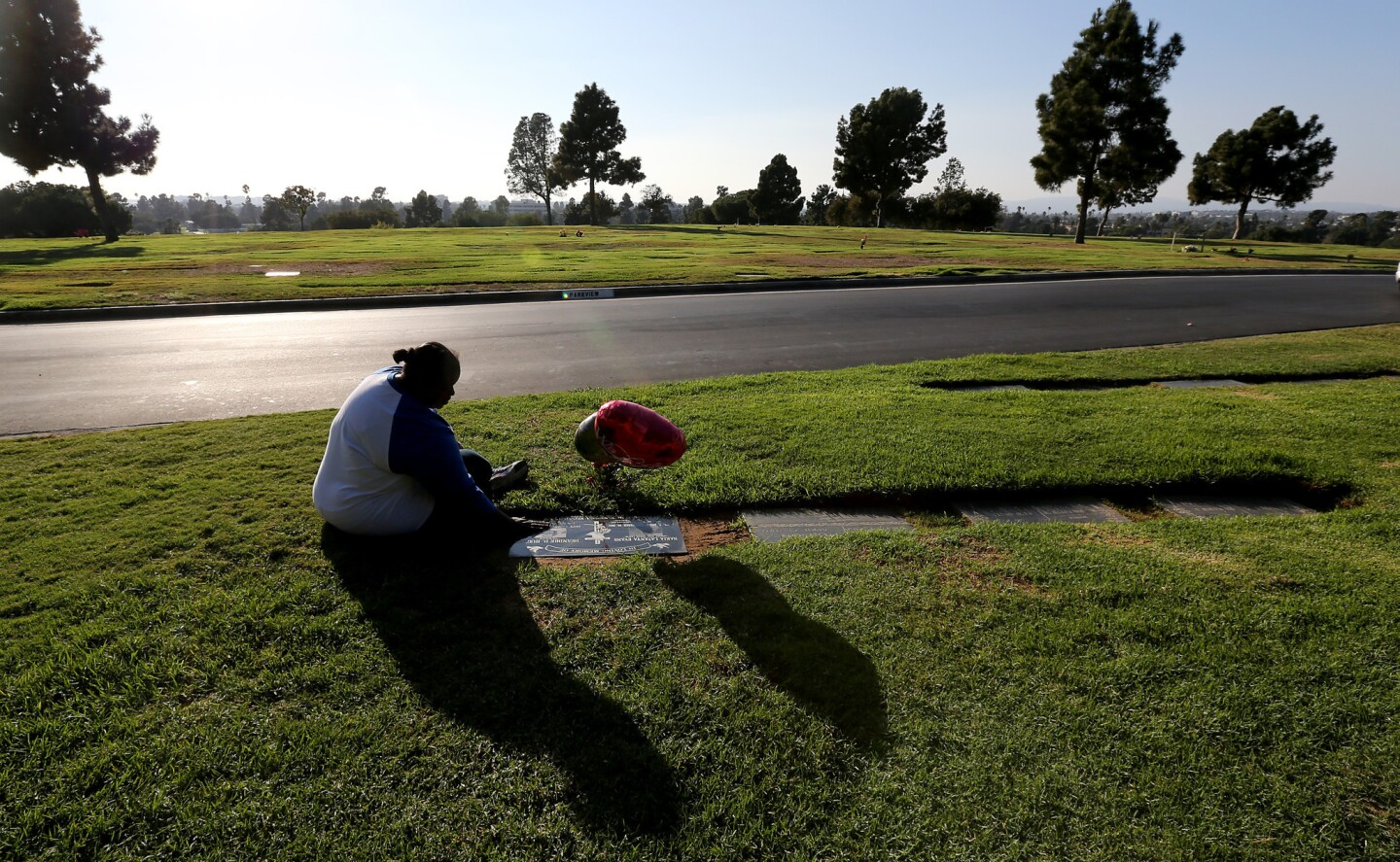 Barbara Pritchett-Hughes sits beside the grave of her son DeAndre Hughes during a visit to Inglewood Park Cemetery in October. Hughes was killed four months earlier at the age of 30. Another son, Dovon Terrell Harris, died in 2007.