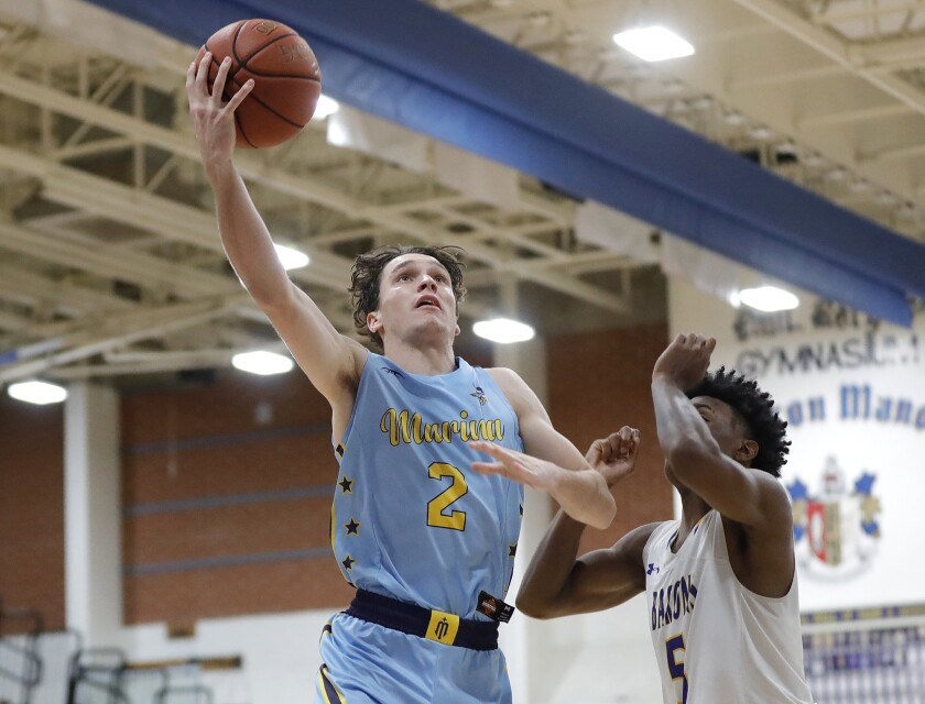 Marina's Eric Hodgkins (2) drives to the basket during a Wave League basketball game against Fountain Valley.
