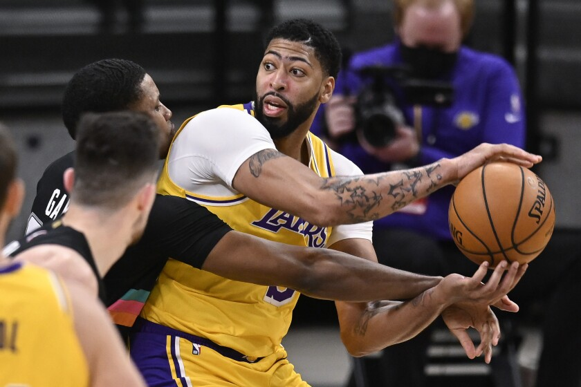 Lakers forward Anthony Davis tries to keep the ball away from San Antonio Spurs forward Rudy Gay.