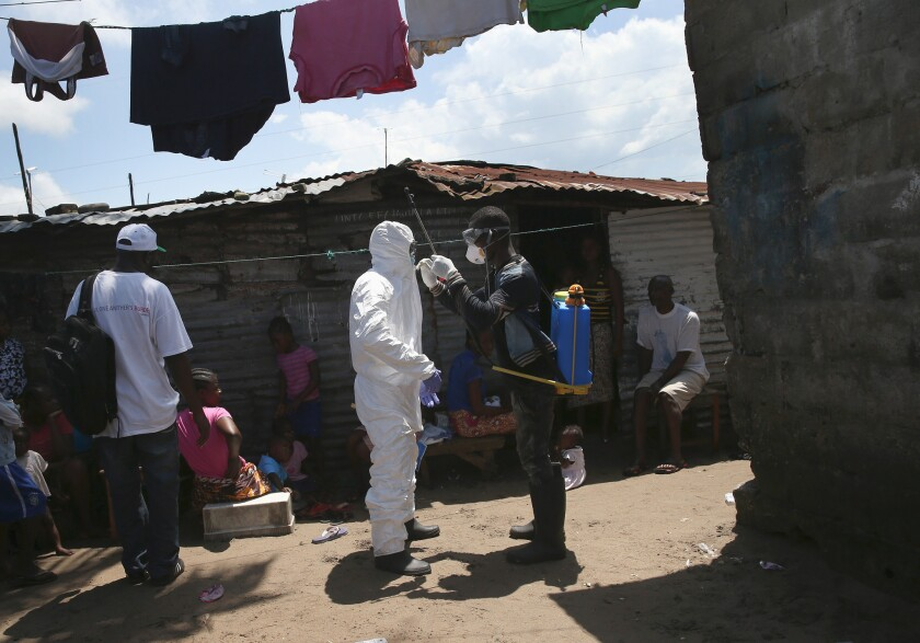 Health workers on Friday suit up in protective clothing in Monrovia, Liberia, before taking people suspected of having Ebola to a reopened Ebola holding center.