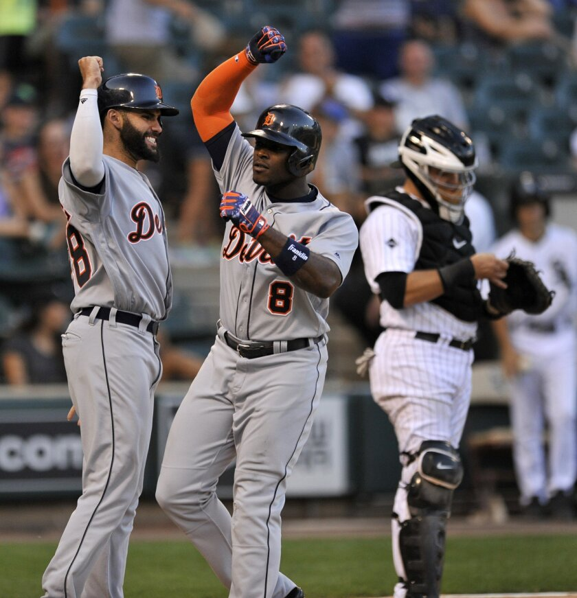 Detroit Tigers' Justin Upton (8) celebrates with teammate Victor Martinez, left, at home plate after hitting a three-run home run during the 11h inning of a baseball game against the Chicago White Sox on Monday, Sept. 5, 2016, in Chicago. (AP Photo/Paul Beaty)