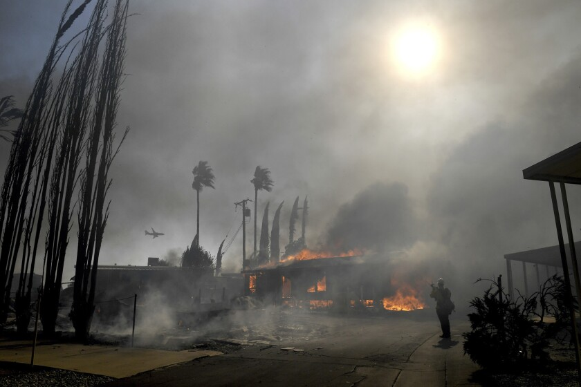 Firefighters battle the Sandalwood Fire as it destroys homes in the Villa Calimesa Mobile Home Park in Calimesa, Calif., on Thursday, Oct. 10, 2019. Burning trash dumped along a road sparked a wildfire Thursday that high winds quickly pushed across a field of dry grass and into a Southern California mobile home park, destroying dozens of residences. (Jennifer Cappuccio Maher/The Orange County Register/SCNG via AP)